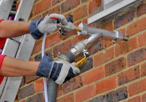 cavity wall insulation being pumped