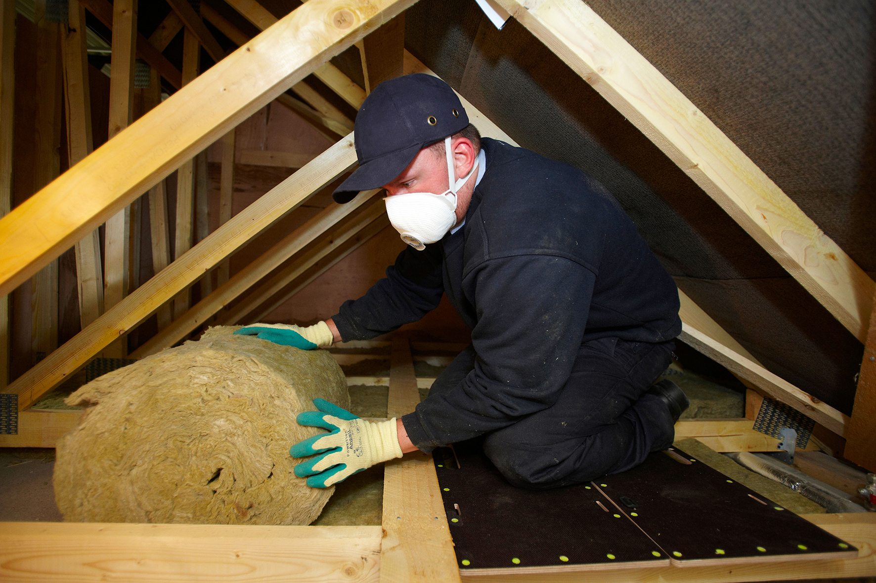 Loft insulation - Man installing loft insulation in a loft