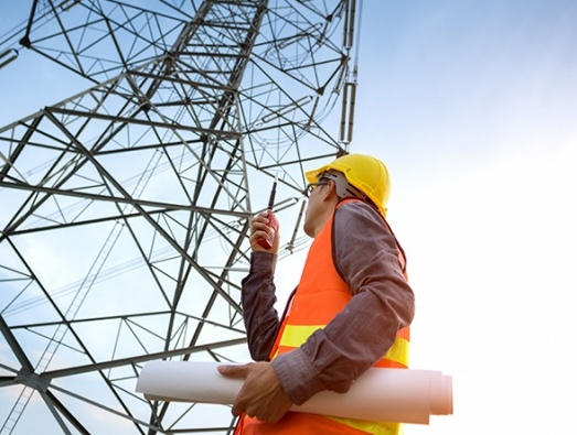 Engineer looking up at a electricity pylon