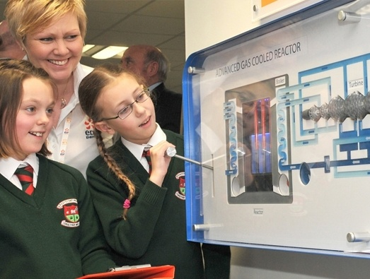 A STEM ambassador looking at an advanced gas cooled reactor model with two pupils