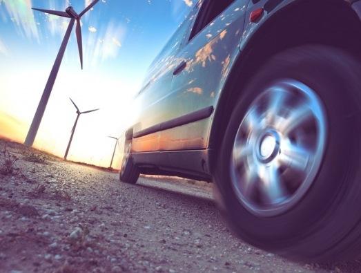 EV car next to wind turbines