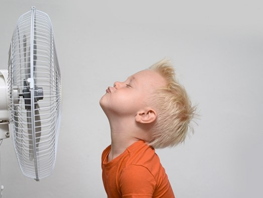 Boy cooling his face with an electric fan