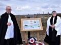 The Vicar of Lydd Rev Chris Maclean, and Curate Rev Jacky Darling, with the updated information board at Dungeness