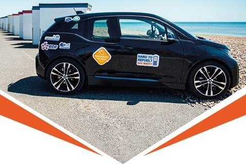 Black BMW i3 parked on a beach and covered in bumper stickers