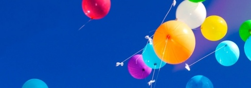 Multi-coloured balloons floating in a blue sky