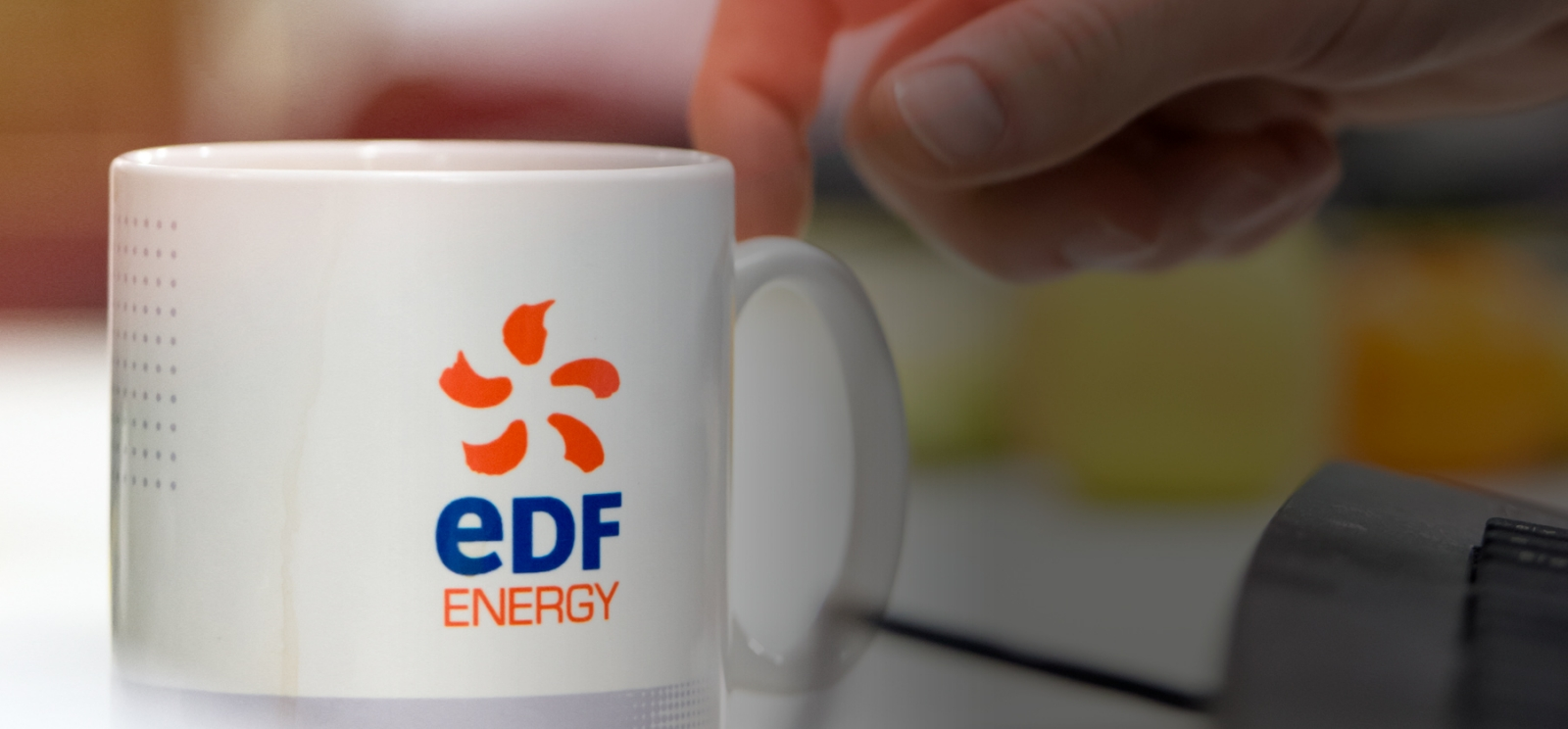 Hand next to an EDF Energy branded coffee mug