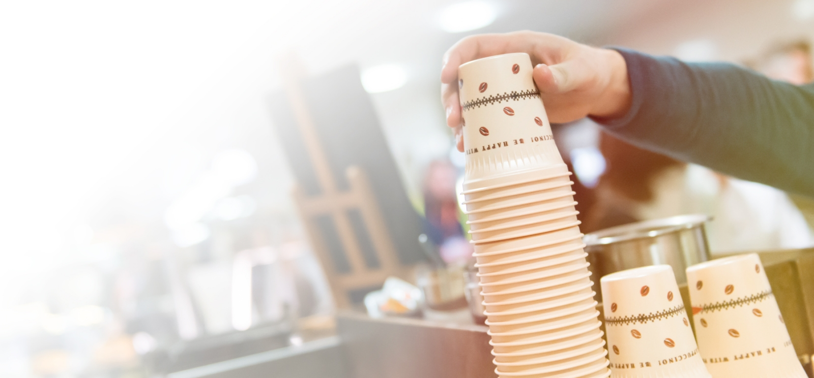 Man taking a new plastic cup from a stack in a kitchen space