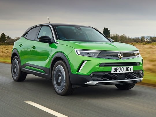 Vauxhall Mokka-e in green driving on a road