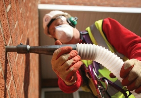 a worker attaches a tube to a brick wall to inject insulation