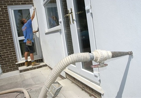 a cavity insulation injection tube is affixed toa wall, while in the background a man measures a doorframe