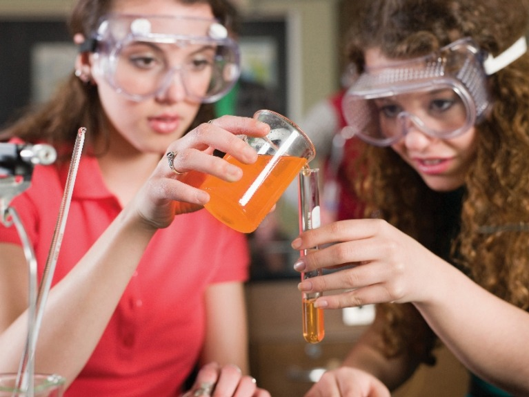 Two girls wearing safety goggles conducting an experiment