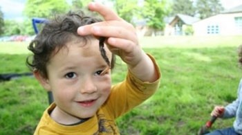 Young boy in yellow t-shirt holds a worm and smiles