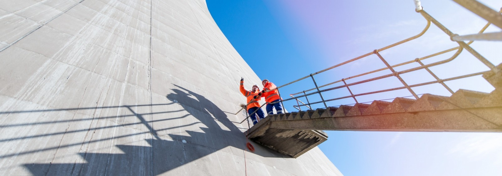 Two male engineers closely inspecting a power station cooling tower