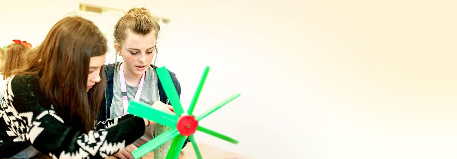 Two girls inspect a model wind turbine