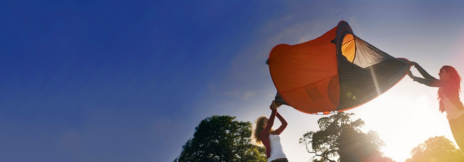 Picture of two girls holding a tent in the air