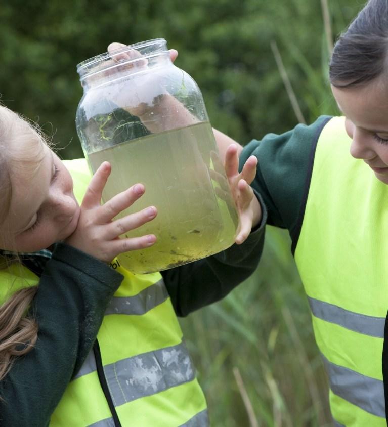 Two school girls looking at pond water sample jar