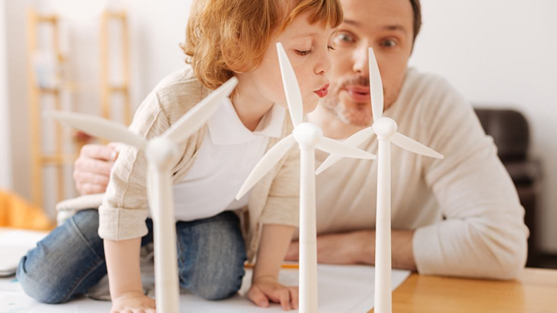 Man and boy looking at a scale model of a wind farm - Alternative energy sources