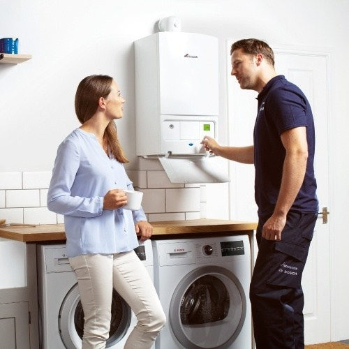 boiler engineer servicing a gas boiler in a home