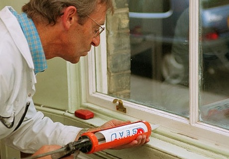 a man uses a glue-gun like apparatus to put draught proofing paste onto a window sill