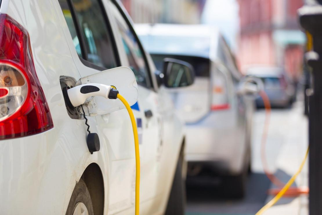 electric cars plugged in on street