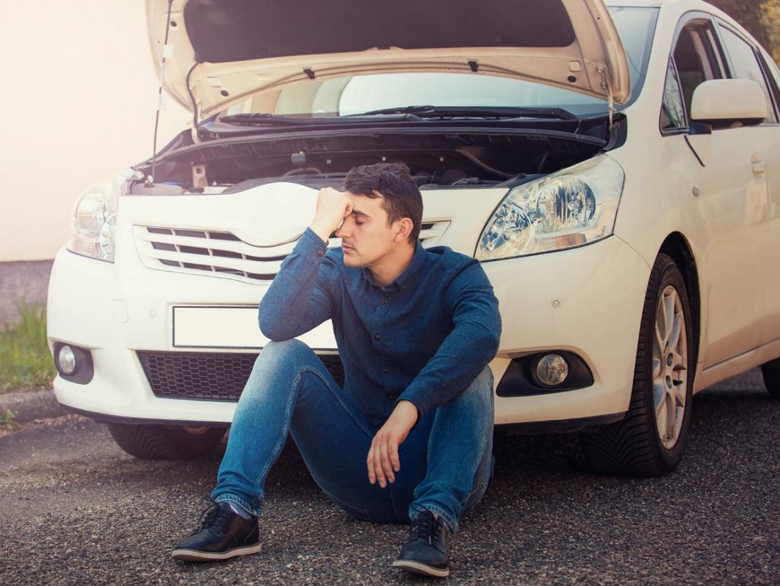 Man with white car broken down requiring maintenance