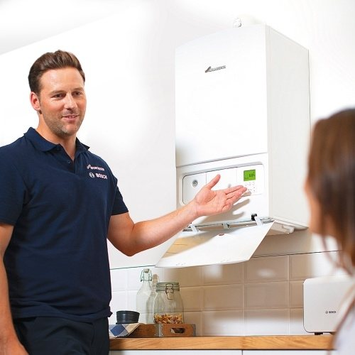gas boiler repair engineer with customer in home explaining the problem with a boiler