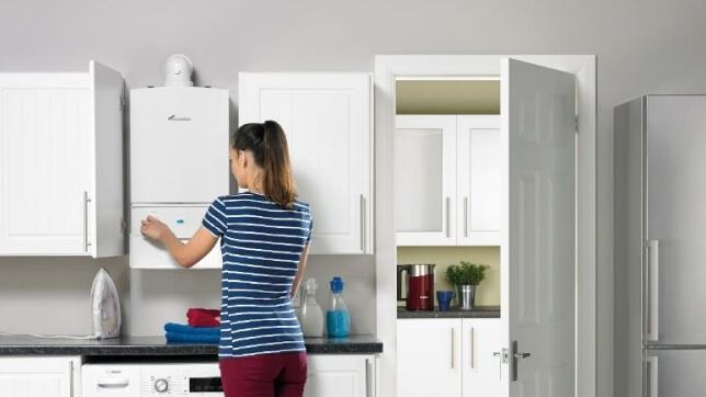 lady in a kitchen with a white gas boiler