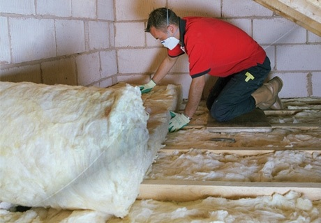 a man wearing a facemask unrolls loft insulation inside a loft