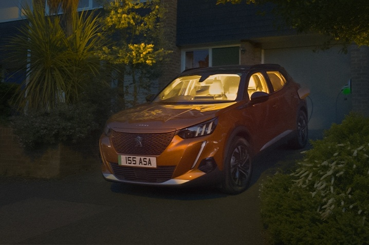 peugeot e2008 in orange at night on a driveway