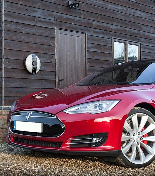 Pod point solo on a barn wall with a red tesla parked next to it