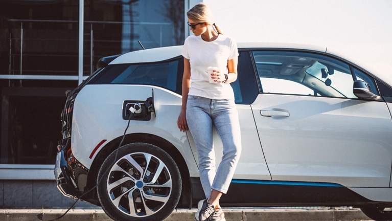woman charging bmw i3 in street