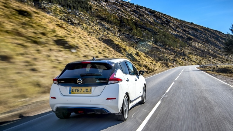 White Nissan Leaf driving on a road