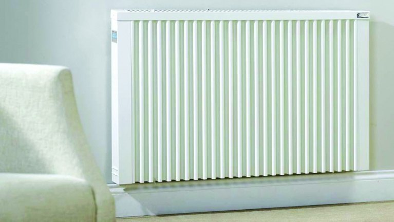 Electric radiator on wall next to a chair