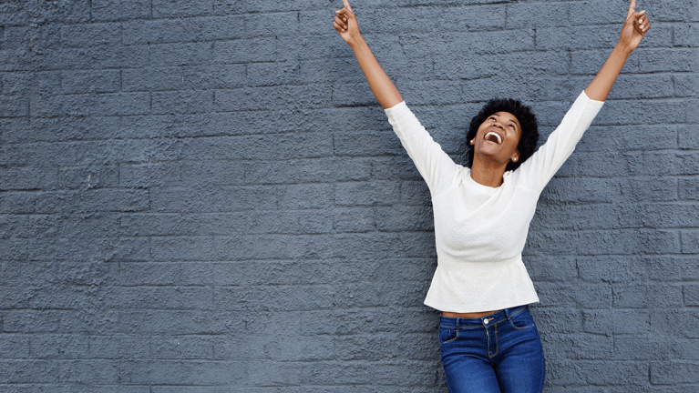 Smiling woman with raised hands looks to the sky