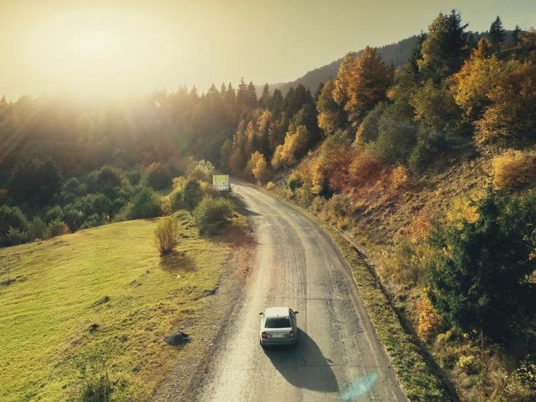 car driving through mountains in autumn