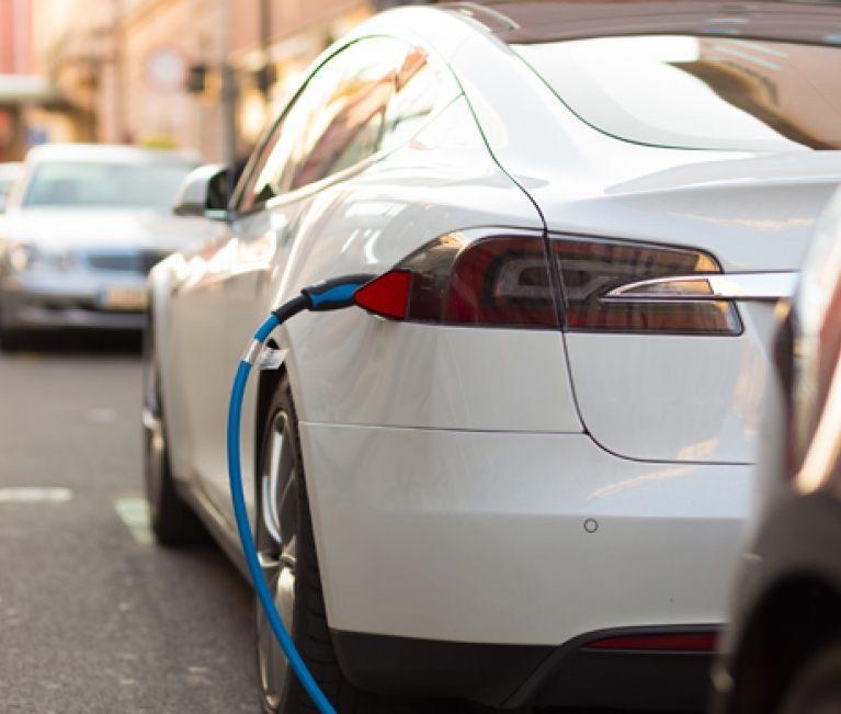white tesla charging in street
