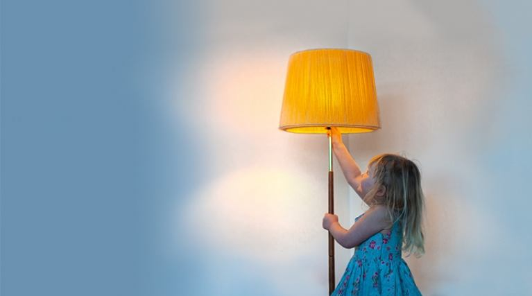 Young girl turning on a lamp