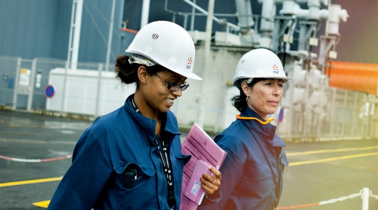 Two female engineers in white hard hats walking outside a power station