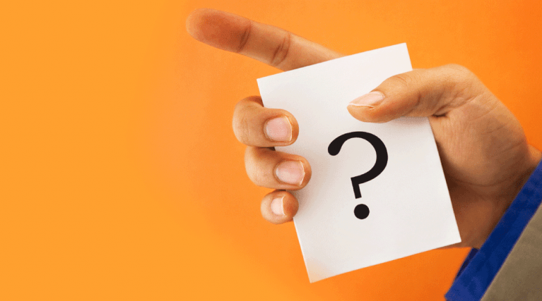 Hand holding card with question mark on it
