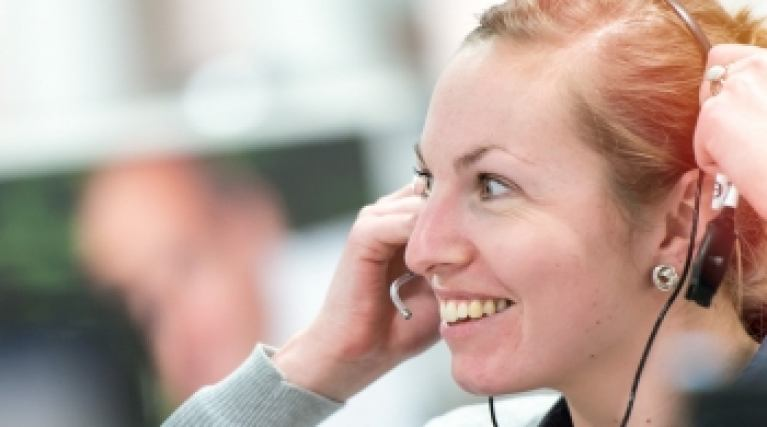Smiling lady in a call centre wearing a headset