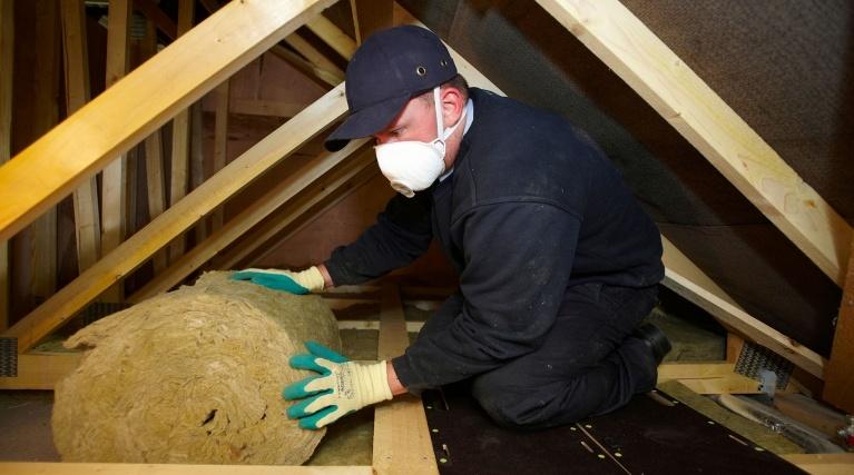 Loft insulation - Man installing loft insulation in a loft