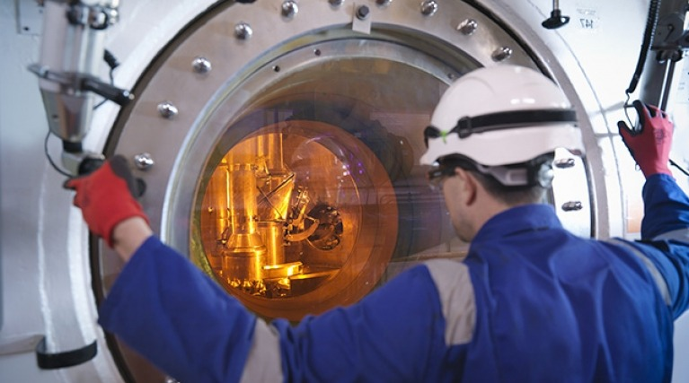 Engineer looking through a restricted porthole viewing pane