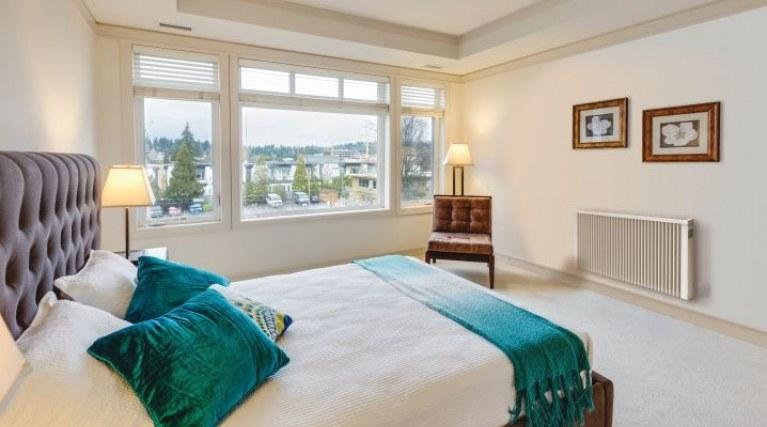 Electric radiator mounted on bedroom wall
