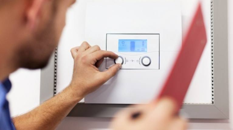 engineer servicing a gas boiler