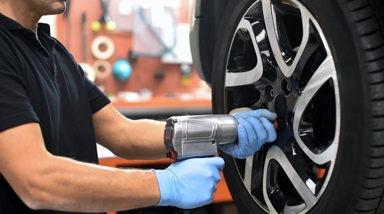 man changing wheel in garage