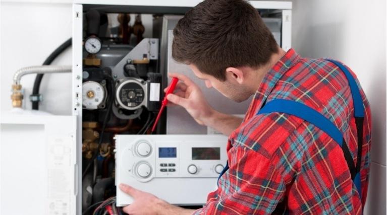 Gas boiler engineer repairing a boiler under insurance