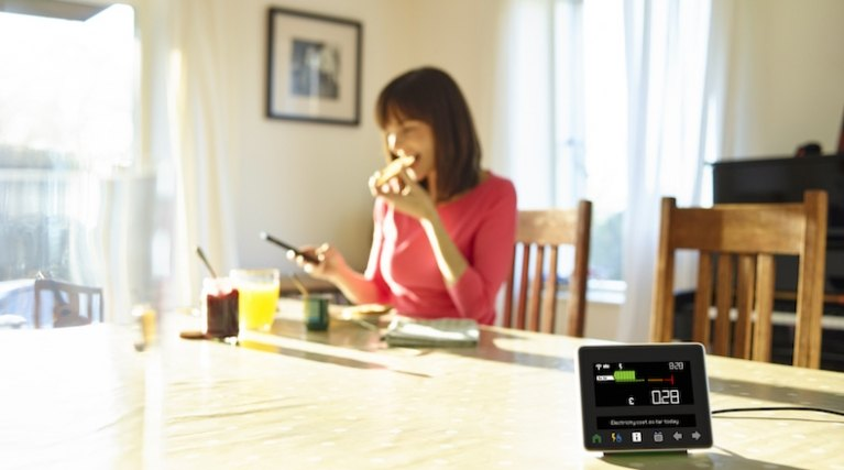 Lady at the kitchen table with smart meter in the foreground