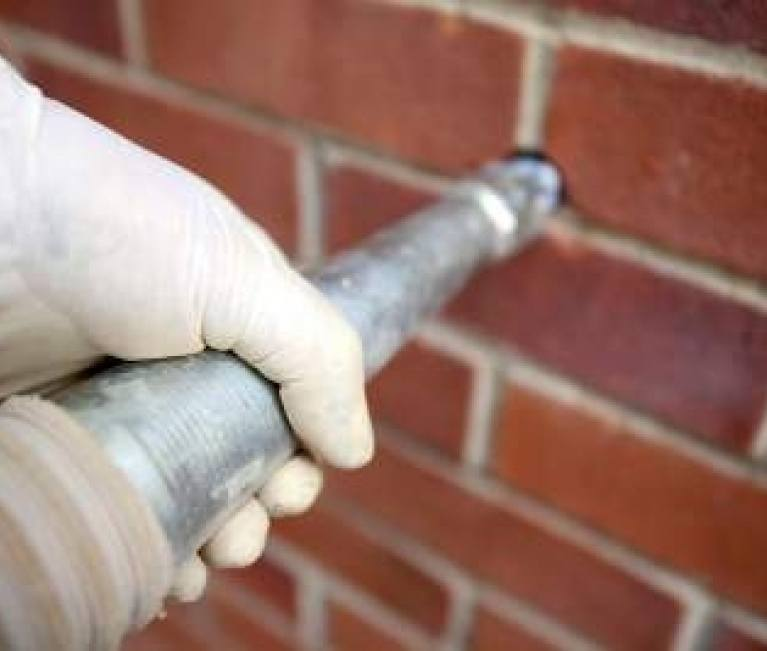 a close up of a cavity wall injection tube affixed to a wall
