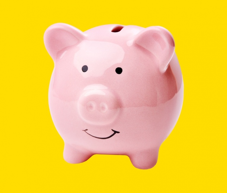 pink piggie bank on yellow background