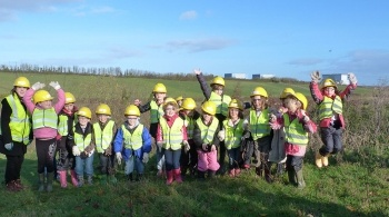 Schoolchildren in yellow hard hats standing in a field